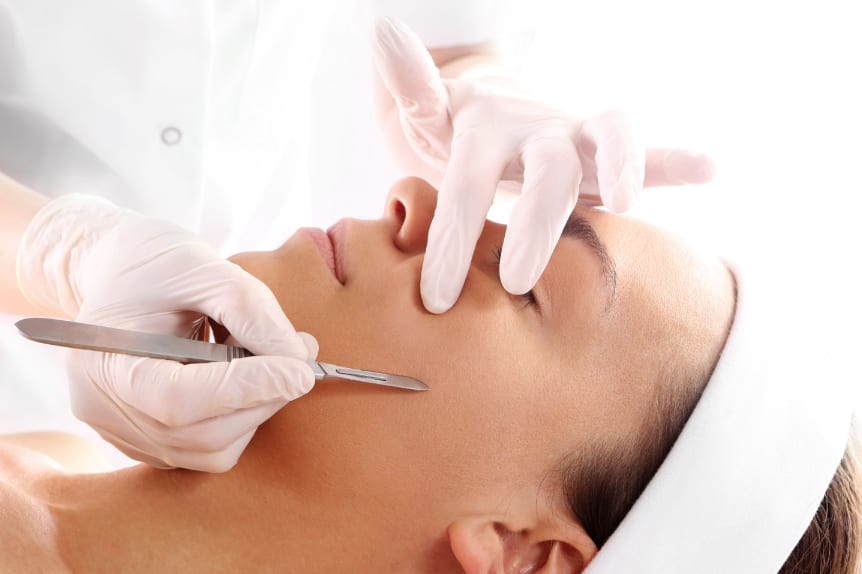 Dermaplaning at Skin Solutions with a doctor working on patient's cheek.