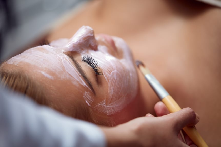 Facials offered at Skin Solutions - Image of woman laying down and getting a facial